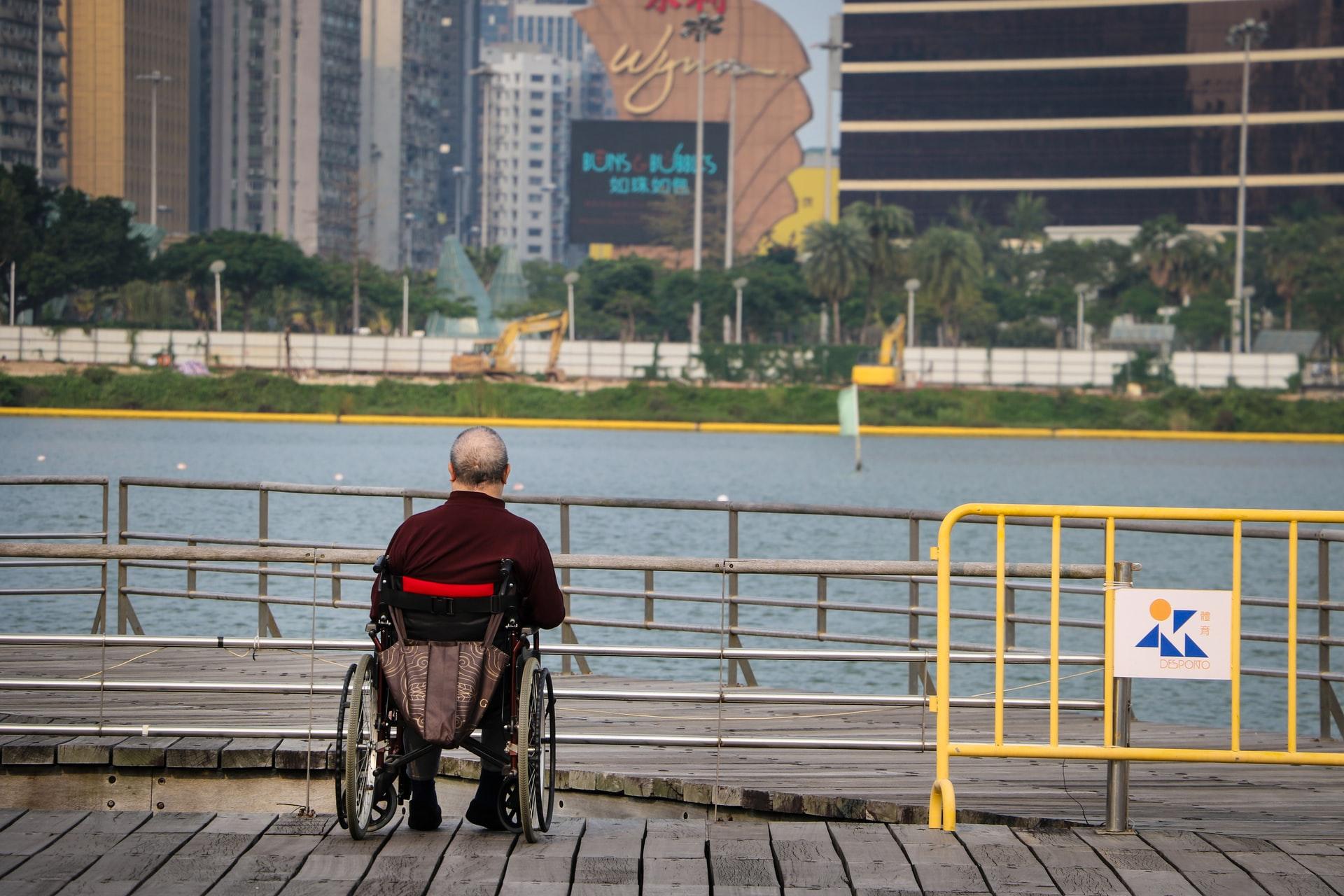 Old man sitting near city river